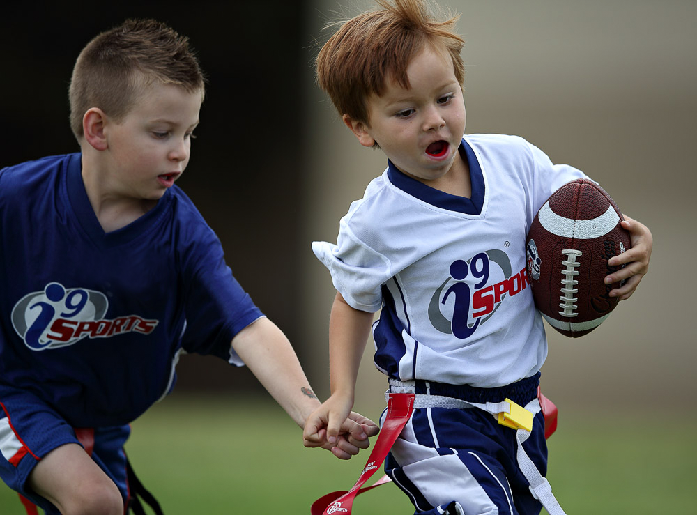 two boys playing flag football at i9 sports game