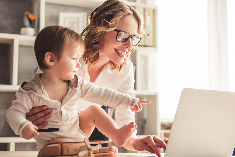 Beautiful business mom is using a laptop and smiling while spending time with her cute baby boy at home