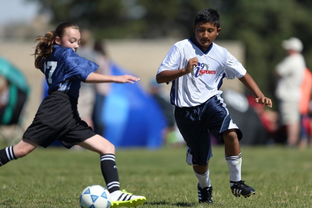 A girl in a blue i9 Sports jersey and a boy in a white i9 Sports jersey compete for a soccer ball on a grassy field.