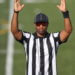 A referee in a black-and-white striped shirt holds up both arms in the symbol for a touchdown.