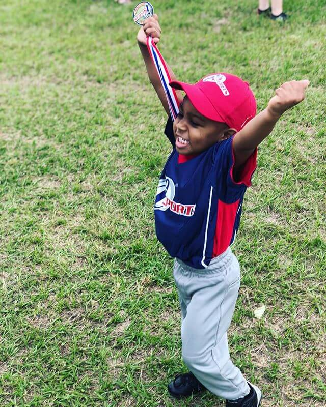 A little boy in a red, white and blue i9 Sports uniform with a baseball cap has both arms outstretched above his head in celebration on a grassy field.