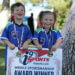 """A boy and girl standing beneath a tree and dressed in i9 Sports jerseys hold a sign that reads, """"i9 Sports i9sports.com Weekly Sportsmanship Award Winner."""" Both are wearing medals around their necks and smiling."""