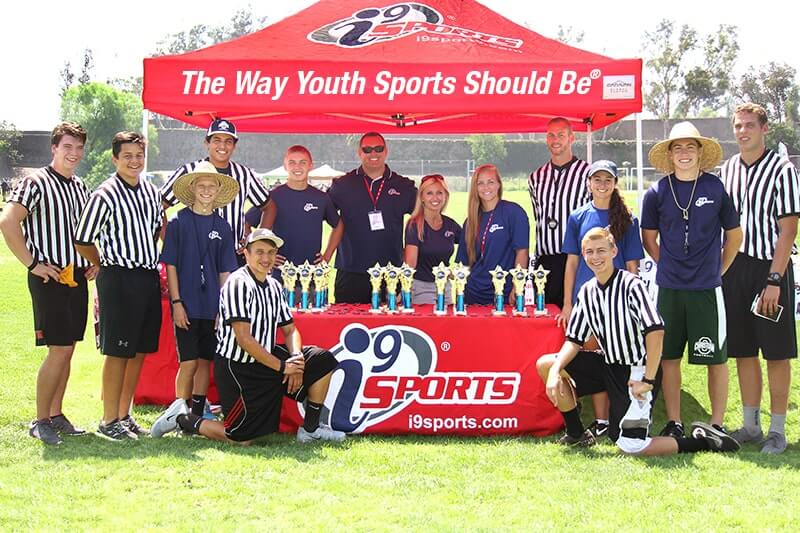 i9 Staff, referees, and coaches stand at a portable gazebo tent